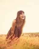 Modelo romântico no vestido de Sun no campo dourado no riso do por do sol Fotografia de Stock Royalty Free