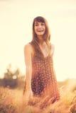 Modelo romântico no vestido de Sun no campo dourado no por do sol Imagem de Stock Royalty Free