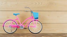 Modelo rosado de la bicicleta del ` s de los niños en el piso marrón de madera Imagen de archivo