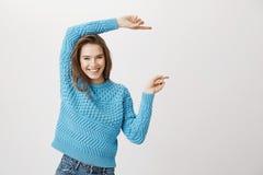 Modelo rubio caucásico feliz positivo que indica a la derecha con ambos índices, sonriendo alegre mientras que se opone a Imagenes de archivo