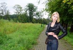 Modelo rubio de la muchacha cerca de un camino en el parque imagenes de archivo