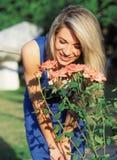 Modelo rubio en el sol brillante que presenta cerca de rosas rosadas fotos de archivo