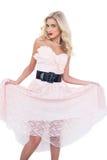 Modelo rubio precioso en el vestido rosado que sostiene vestido Foto de archivo libre de regalías