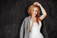 Modelo rubio sonriente hermoso de la mujer en abrigo oscuro elegante y el vestido blanco fotografía de archivo libre de regalías