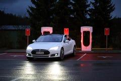 Modelo S Arrives de Tesla en la estación del sobrealimentador en la noche Imágenes de archivo libres de regalías