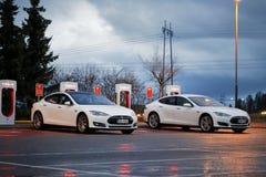 Modelo S Cars Plugged de dos Tesla adentro en la estación del sobrealimentador Imágenes de archivo libres de regalías