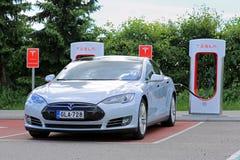 Modelo S de Tesla en la estación del sobrealimentador Fotos de archivo libres de regalías