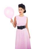Modelo satisfeito do cabelo preto que guarda um balão cor-de-rosa Foto de Stock Royalty Free