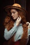 Modelo sensual del pelirrojo con los ojos cerrados en el sombrero de paja que presenta en el PA Fotos de archivo