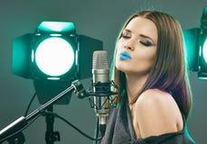 Modelo sensual joven que canta en un micrófono Mujer de la belleza Foto de archivo libre de regalías