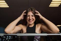 Modelo 'sexy' bonito da aptidão que levanta emocionalmente no barbell atlético no gym imagens de stock royalty free