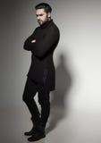 Modelo 'sexy' do homem da forma na camiseta, em calças de brim pretas e no levantamento das botas dramático Foto de Stock Royalty Free