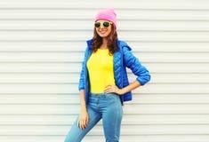 Modelo sonriente bonito de la mujer de la moda del retrato en la ropa colorida que presenta sobre el fondo blanco las gafas de so Fotos de archivo