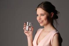 Modelo sonriente con el vidrio de agua Cierre para arriba Fondo gris Imagen de archivo libre de regalías