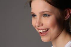 Modelo sonriente con maquillaje Cierre para arriba Fondo gris Imagen de archivo libre de regalías