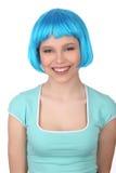 Modelo sonriente que presenta con la peluca azul Cierre para arriba Fondo blanco Foto de archivo