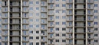 Modelo texturizado de una pared residencial de la construcción de viviendas del whitestone ruso con muchas ventanas y del balcón  Foto de archivo libre de regalías