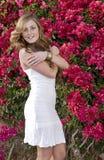 Modelo triguenho bonito na frente das flores Fotografia de Stock Royalty Free