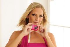 Modelo usando cámara rosada del juguete Imagenes de archivo