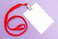 Modelo vazio do crachá isolado no roxo Zombaria vazia lisa da etiqueta do nome acima com corda vermelha fotos de stock royalty free