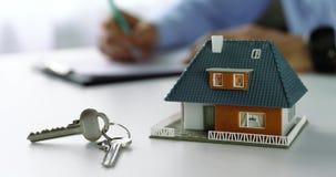 Modelo y llaves de escala de la casa en la tabla en la oficina del agente inmobiliario metrajes