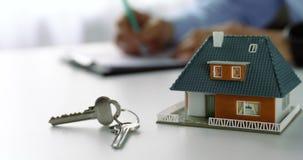 modelo y llaves de escala de la nueva casa en la tabla en la oficina del agente inmobiliario almacen de metraje de vídeo