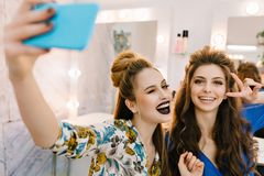 Modelos atractivos elegantes del retrato dos elegantes con los makeups elegantes, tocados de lujo que hacen el selfie en sal?n de foto de archivo