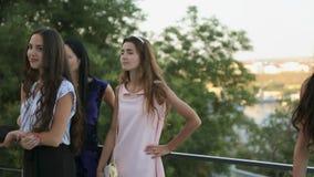 Modelos atractivos en los vestidos que presentan en el al aire libre almacen de metraje de vídeo