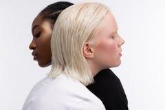Modelos con diverso color de la piel y del pelo que abraza mientras que presenta fotografía de archivo libre de regalías