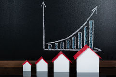 Modelos da casa em Front Of Blackboard Showing Graph Imagem de Stock Royalty Free