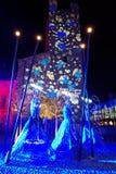Modelos de la luz en la torre con ángeles estilizados en la calle Imágenes de archivo libres de regalías