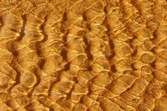 Modelos de la ondulación del mar sobre la arena de oro fotografía de archivo libre de regalías