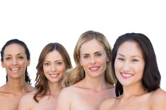 Modelos desnudos sonrientes que presentan en una línea con morenita en fondo Imagenes de archivo