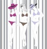 Modelos em ternos de banho em um fundo listrado Imagem de Stock Royalty Free