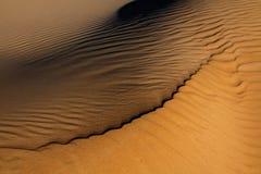 Modelos en la arena creada por el viento Imagenes de archivo