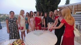 Modelos en los vestidos que beben el champán en la terraza en el restaurante almacen de video
