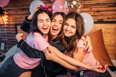 Modelos jovenes alegres y felices que se abrazan Se sientan en cama en sitio juntos y miran en cámara adolescentes foto de archivo libre de regalías