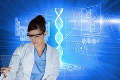 Modelos médicos que vestem os vidros de segurança que olham a corrediça do microscópio contra o fundo azul dos gráficos Fotografia de Stock Royalty Free