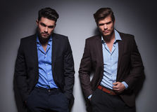 Modelos masculinos serios que presentan contra la pared gris Imagenes de archivo