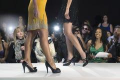 Modelos nos saltos altos contra espectadores Fotos de Stock