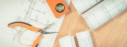 Modelos o diagramas eléctricos y herramientas anaranjadas del trabajo para el uso en trabajos del ingeniero Imagenes de archivo