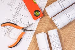 Modelos o diagramas eléctricos y herramientas anaranjadas del trabajo para el uso en trabajos del ingeniero Imagen de archivo libre de regalías