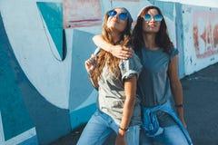 Modelos que llevan la camiseta llana y las gafas de sol que presentan sobre wa de la calle Fotos de archivo libres de regalías
