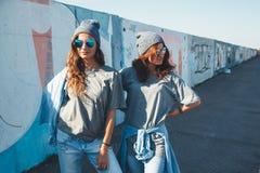 Modelos que llevan la camiseta llana y las gafas de sol que presentan sobre wa de la calle Fotos de archivo
