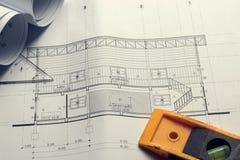 Modelos y rollos del modelo e instrumentos de un dibujo arquitectónicos en la mesa de trabajo Imagen de archivo