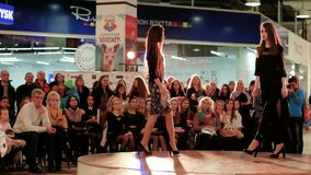 Models defile on runway, two young girls showcasing new collection on catwalk, fashion show. Kherson, Ukraine 23 April 2016: Fabrika Fashion Weekend models stock video footage