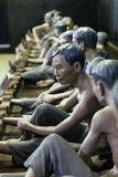 Models of detained prisoners by lock their foot ankle on something like wooden console at Hoa Lo Prison Museum in Hanoi, Vietnam Stock Images