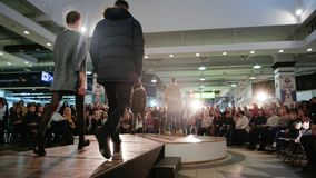 Models going down runway, man and woman showcasing designs, fashion show, models in spotlight