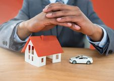 Models hands protective over house and car. Digital composite of Models hands protective over house and car Royalty Free Stock Images