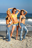 Models posing on the beach. Three models pose on a beach stock photos